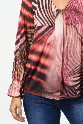 Μπλούζα ριχτή με εμπριμέ, τιγρέ σχέδιο. Μακριά μανίκια με λάστιχο και βολάν στους καρπούς, V λαιμό και ιδιαίτερο σχέδιο γραβάτα.